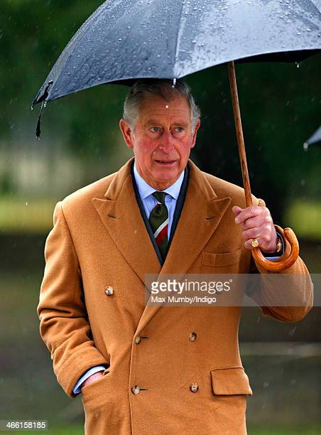 Prince Charles Prince of Wales shelters under an umbrella as he visits The Church of St John the Evangelist in Shobdon on January 31 2014 near...