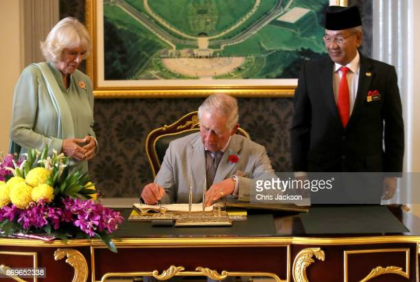 Prince Charles Prince of Wales signs the visitors book as Camilla Duchess of Cornwall looks on ahead of Tea with His Majesty The Yang diPertuan Agong...