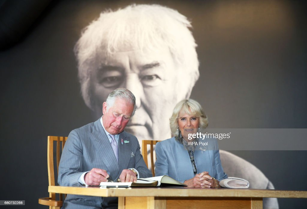 Prince Charles, Prince of Wales signs the visitors book while Camilla, Duchess of Cornwall looks on during a tour of the new centre in Bellaghy, dedicated to Seamus Heaney during their visit on May 9, 2017 in Bellaghy, Northern Ireland..