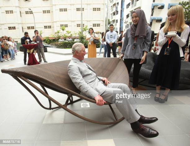 Prince Charles Prince of Wales sits on an outdoor rocking daybed designed by students during his visit to the Nanyang Academy of Fine Arts on...