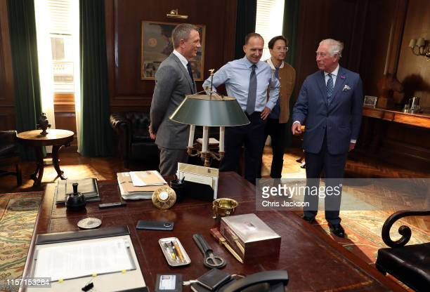 Prince Charles, Prince of Wales speaks to actors Daniel Craig, Ralph Fiennes and director Cary Joji Fukunaga during a visit to the James Bond set at...