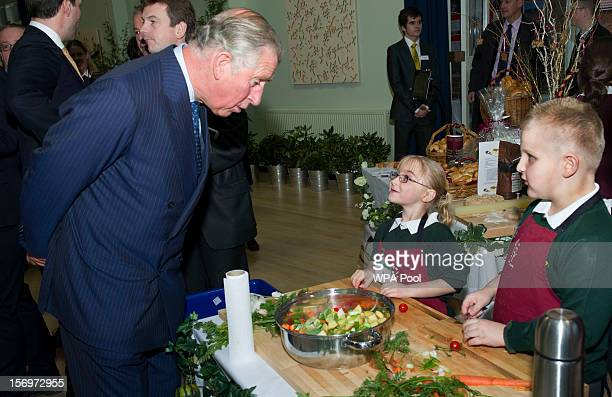 Prince Charles Prince of Wales speaks to young pupils during a visit to Carshalton Boys Sports College with Jamie Oliver to see how the school has...