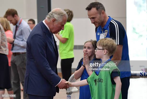 Prince Charles Prince of Wales speaks with children engaged in sporting activities during a visit to Ulster University's Colraine Campus on June 12...