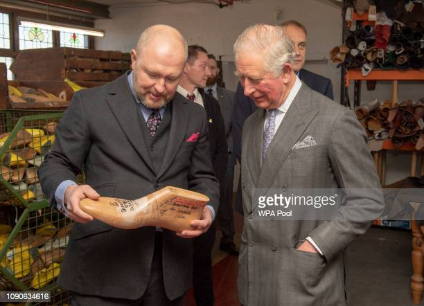 Prince Charles Prince of Wales speaks with Michael James who shows the Prince the size 22 shoe last for US Basketball star Shaquille O'Neal as he...