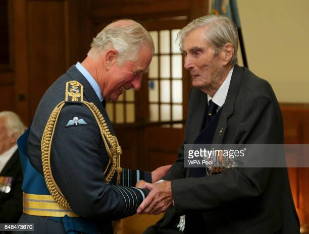 Prince Charles Prince of Wales talks to Battle of Britain veteran Wing Commander Paul Farnes during a reception following a service marking the 77th...
