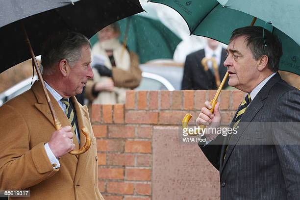 Prince Charles, Prince of Wales talks to Gerald Grosvenor, Duke of Westminster as they shelter under umbrellas during a visit to Aldford Villiage...
