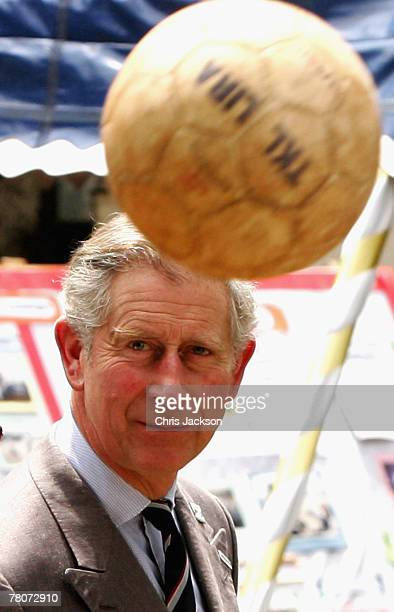Prince Charles Prince of Wales throws a football as he tours Kawempe Slum on November 23 2007 in Kampala Uganda The Prince is in Uganda with his wife...