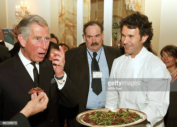 Prince Charles, Prince of Wales tries some beef prepared by chef Carlo Cracco during an organic food reception at the British Ambassador's residence...