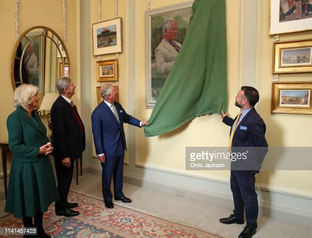 Prince Charles Prince of Wales unveils a painting of himself a portrait by artist Gareth Reid during the reopening of Hillsborough Castle on April 09...