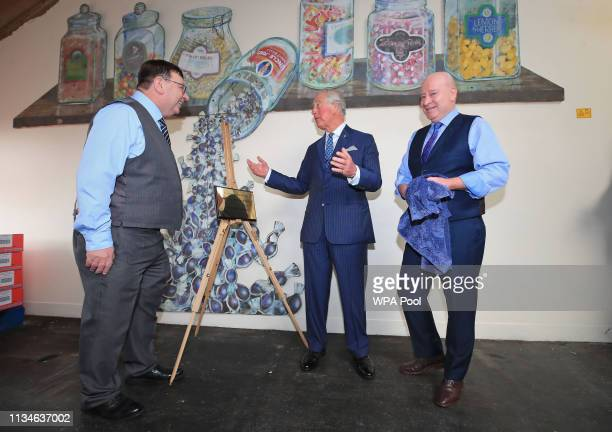 Prince Charles Prince of Wales unveils a plaque as he tours the Toffee Works to celebrate 100 years of the familyrun William Santus Co Ltd's factory...