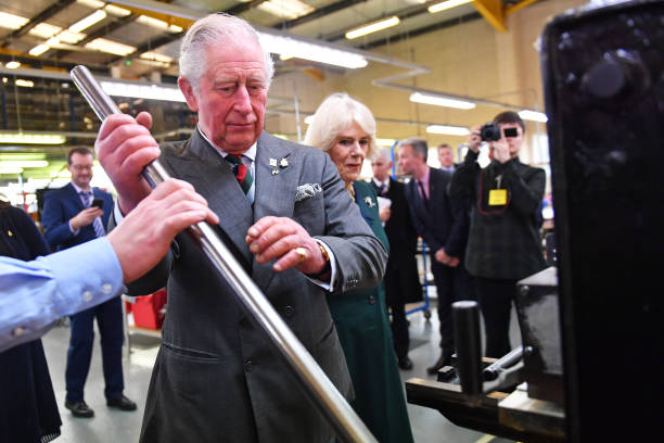 Prince Charles Prince of Wales uses a leather press during a visit to The Cambridge Satchel Company where he toured the company's workshops and met...