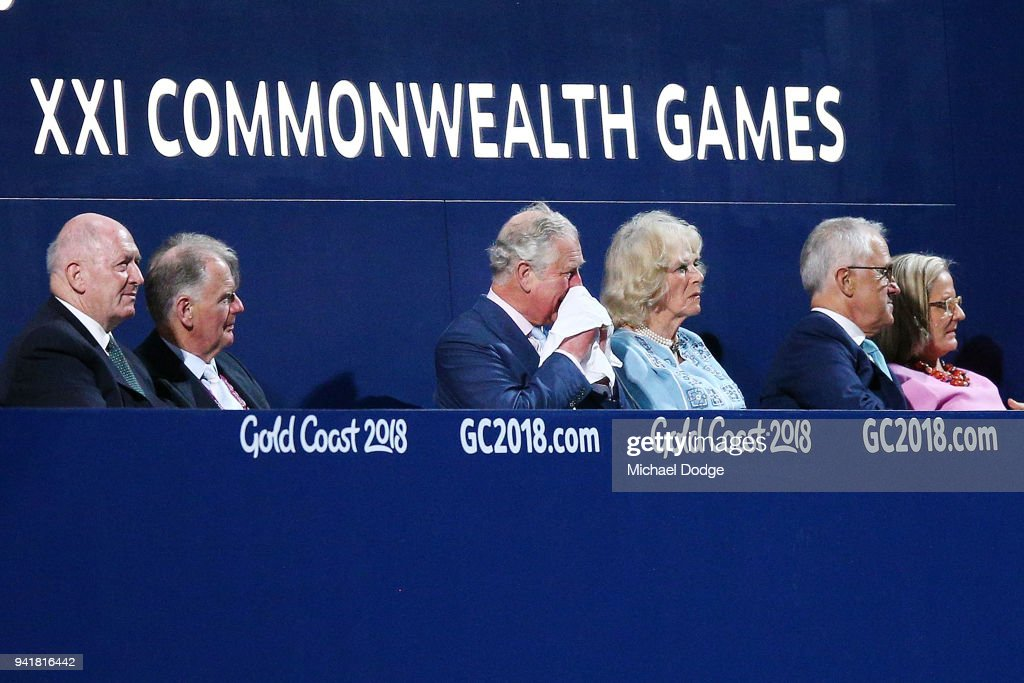 Prince Charles, Prince of Wales uses his hankerchief next to his wife Camilla, Duchess of Cornwall and Australian Prime Minister Malcom Turnbull (R) during the Opening Ceremony for the Gold Coast 2018 Commonwealth Games at Carrara Stadium on April 4, 2018 on the Gold Coast, Australia.
