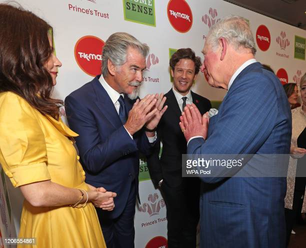 Prince Charles, Prince of Wales uses the Namaste gesture to greet Anna Friel and Pierce Brosnan as he attends the Prince's Trust And TK Maxx &...