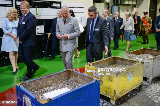 Prince Charles Prince of Wales walks past hoppers full of foreign currency that is made on the minting factory floor during a tour of The Royal...