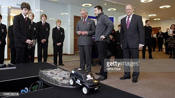 Prince Charles Prince of Wales watches a pupil from Wilmslow High School driving a remote control car during a visit the Jaguar Land Rover Education...