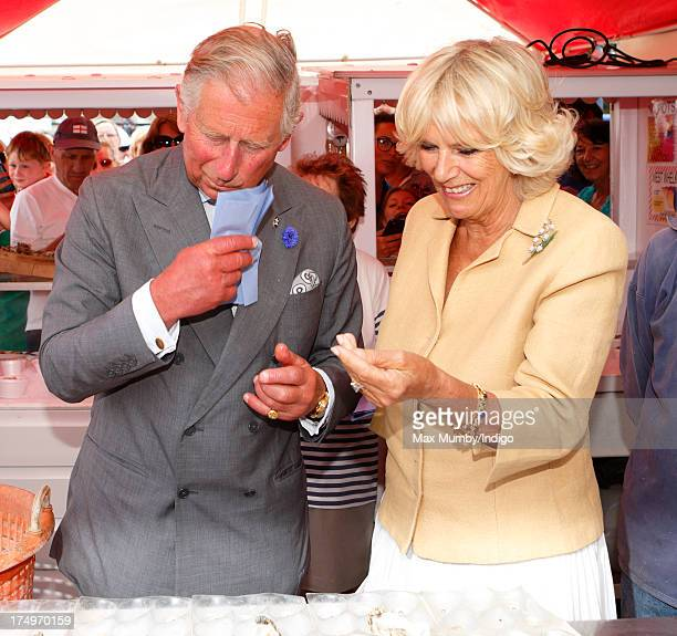 Prince Charles Prince of Wales wipes his mouth after eating an oyster as he and Camilla Duchess of Cornwall visit the Whitstable Oyster Festival on...