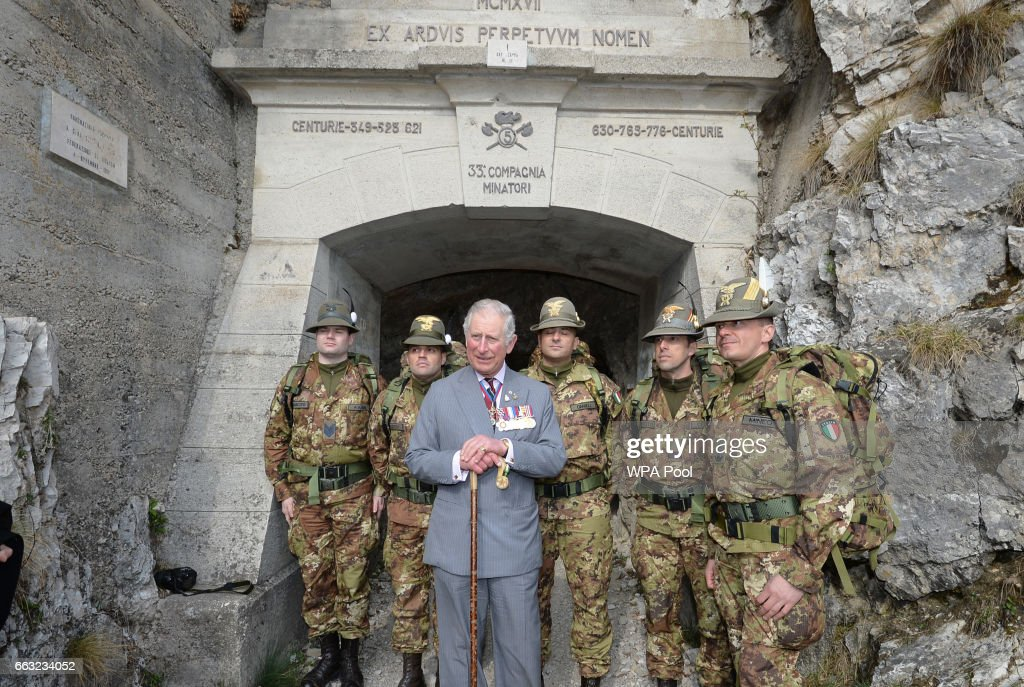 Prince Charles, Prince of Wales with soldiers from Italy's Alpini mountain warfare military corps at the entrance to a tunnel high in the Dolomite Moutains where British soldiers fought alongside Italians against the Austrians in the First World War on April 1, 2017 in Northern Italy. Photo by John Stillwell/WPA Pool/Getty Images)