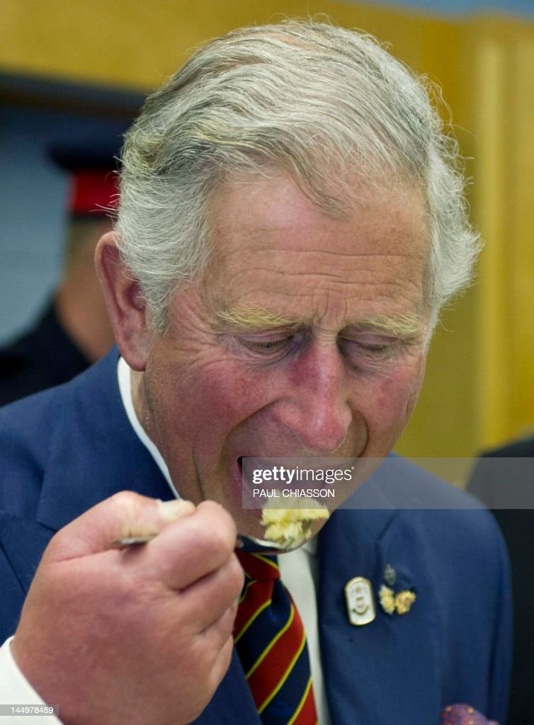 Prince Charles samples a cake while touring the Hazen White-St Francis School in Saint John, New Brunswick, on Monday, May 21, 2012. The royal couple are on a four-day visit to Canada to mark the Queen's Diamond Jubilee. AFP PHOTO / Pool / Paul Chiasson
