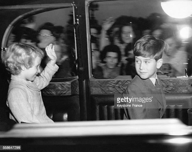 Prince Charles se retourne pour regarder la Princesse Anne saluant la foule alors qu'ils quittent le Palais de Buckingham en voiture le 9 aout 1956 a...