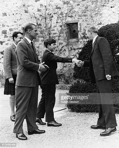 Prince Charles shakes hands with Robert Chew the headmaster of Gordonstoun School on his first day as a pupil there He is accompanied by his father...