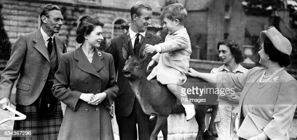 Prince Charles sitting on a statue watched by King George VI Princess Elizabeth the Duke of Edinburgh Princess Margaret and Queen Elizabeth while on...