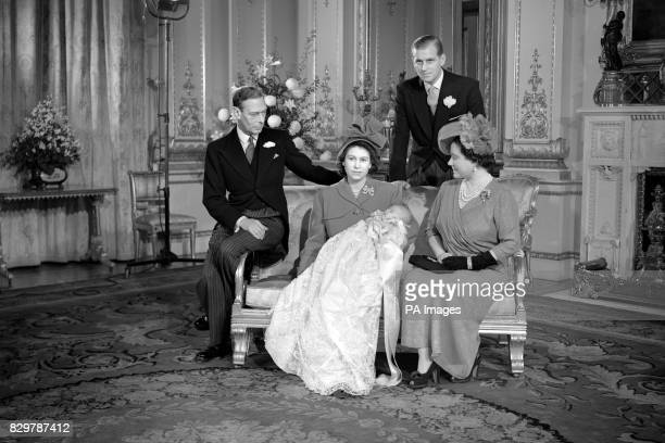 Prince Charles sleeps in the arms of his mother Princess Elizabeth after his Christening at Buckingham Palace Looking on are left King George VI The...