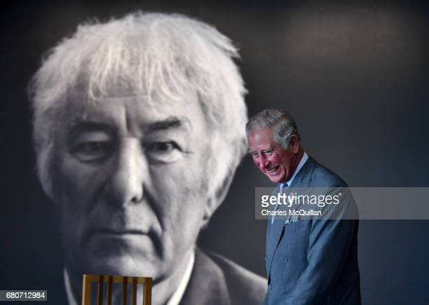 Prince Charles smiles as he walks past a portrait of the late Seamus Heaney during his visit to Seamus Heaney Home Place along with the Duchess of...