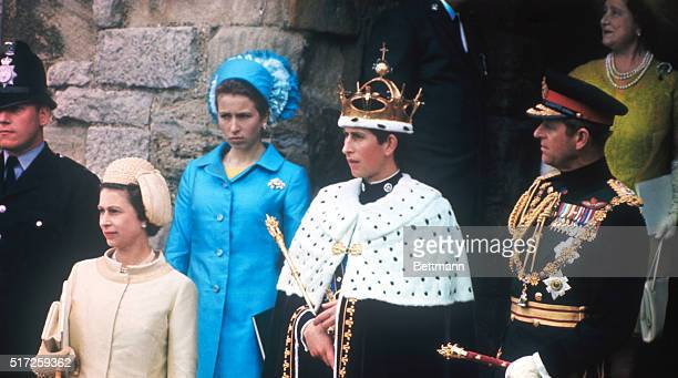 Prince Charles stands on castle steps after being invested as Prince of Wales He is flanked by his mother Queen Elizabeth II and father Prince Philip...