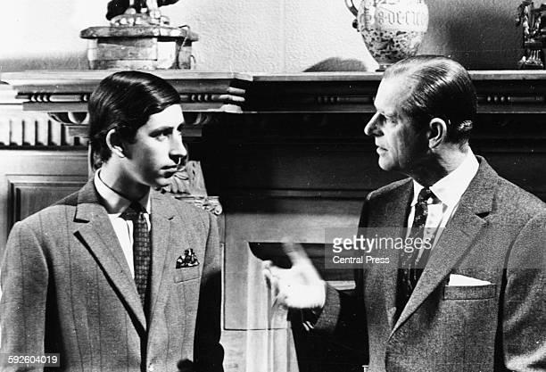 Prince Charles talking to his father the Duke of Edinburgh in front of a fireplace at Sandringham Scotland 1969