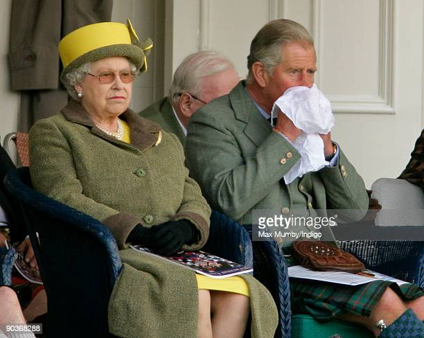 HRH Prince Charles The Prince of Wales blows his nose as he and HM Queen Elizabeth II attend the 2009 Braemar Royal Highland Gathering in The...