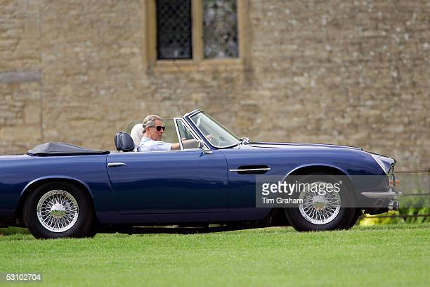 Prince Charles the Prince of Wales drives his Aston Martin Volante convertible sports car to polo at Cirencester on June 17 2005 in Cirencester...