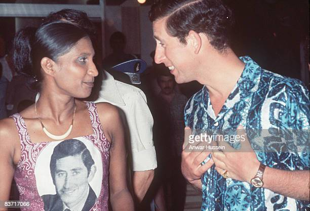 Prince Charles the Prince of Wales is amused to meet a fan with his portrait painted on her dress when he arrives in West Africa in 1977