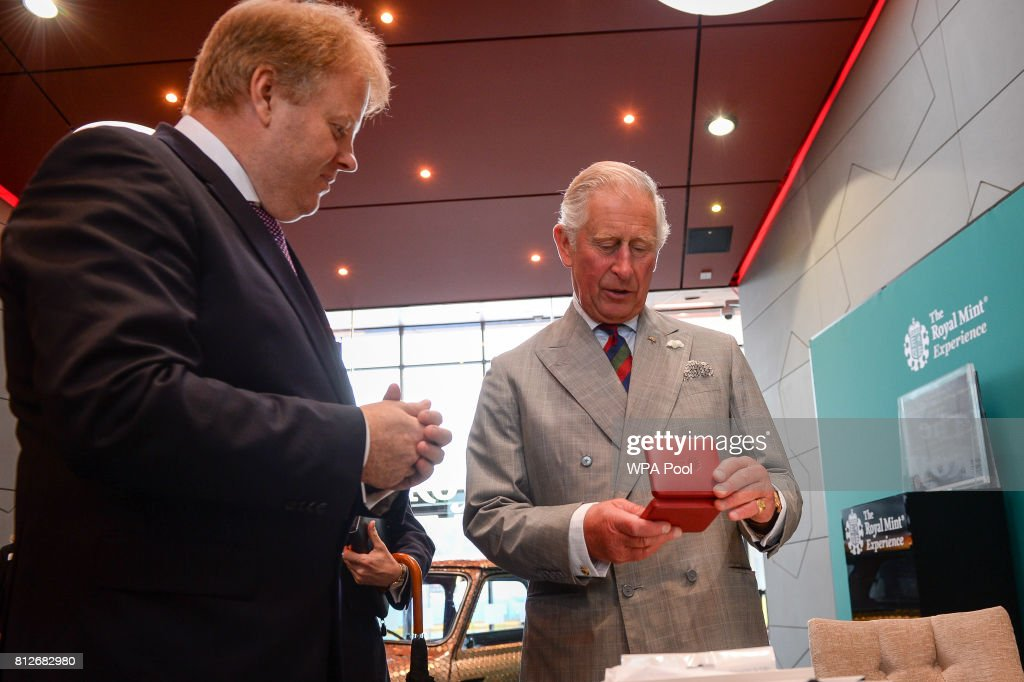 Prince Charles, The Prince of Wales is presented the new commemorative £5 coin, celebrating the Duke of Edinburgh's lifetime in the public service, that the Prince struck himself, by Royal Mint CEO Adam Lawrence during a tour of The Royal Mint's visitor centre on July 11, 2017 in Heol-Y-Sarn, Wales.