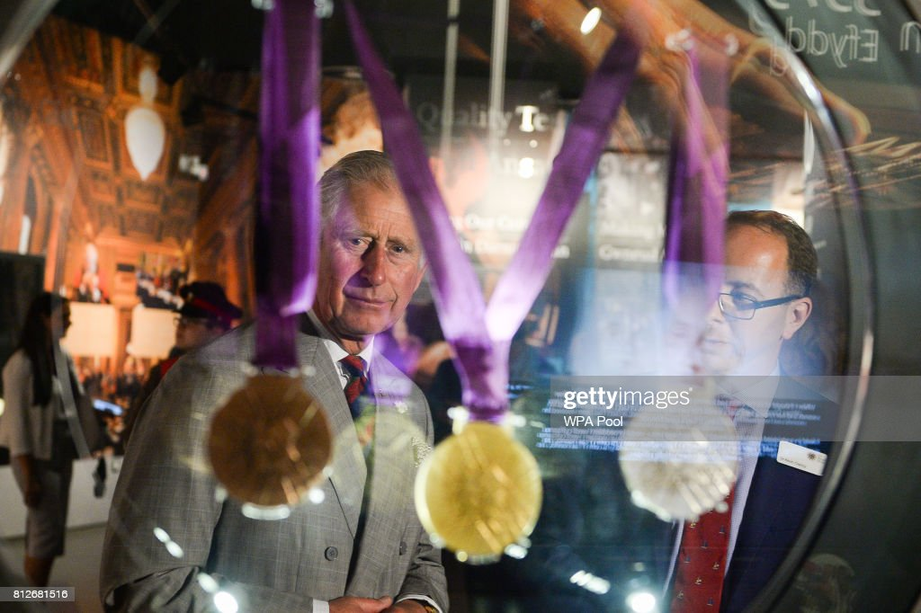 Prince Charles, The Prince of Wales is shown London 2012 medals in a glass case by the Director of the Royal Mint Museum Dr Kevin Clancy during a tour of The Royal Mint's visitor centre on July 11, 2017 in Heol-Y-Sarn, Wales.