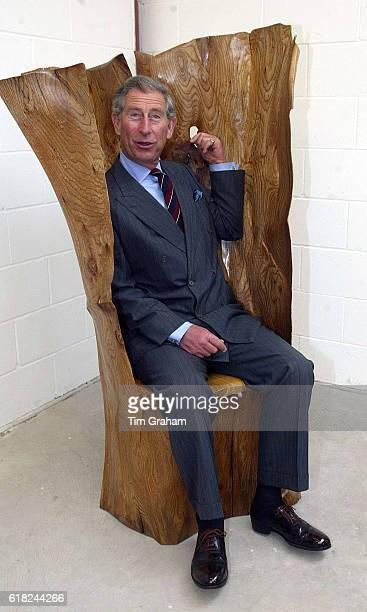 Prince Charles the Prince of Wales jokes while he sits in a handcrafted £10500 'paper heart' chair during a visit to MJ cabinetmakers studio in...