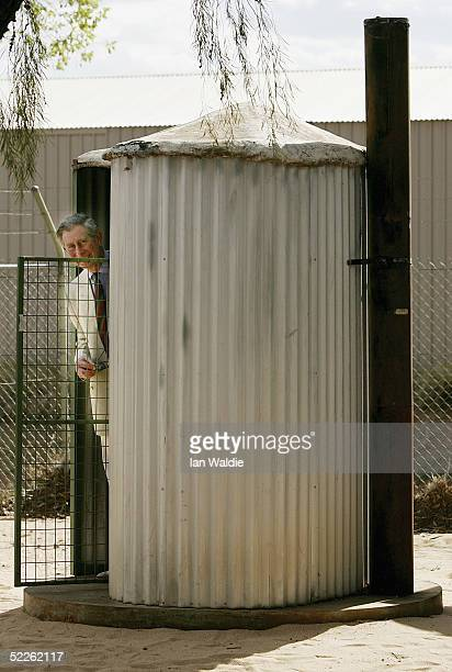 Prince Charles the Prince of Wales peers out of an outback toilet as he visits the Centre of Appropriate Technology March 2 2005 in Alice Springs...