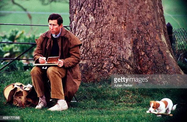 Prince Charles The Prince of Wales sketching on the bank of the River Thames at Windsor Castle accompanied by his dogs on March 23 1989 in Windsor...
