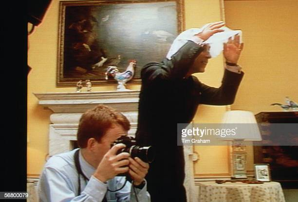 Prince Charles tries to get the attention of Princes William and Harry while photographer Tim Graham photographs them at Kensington Palace