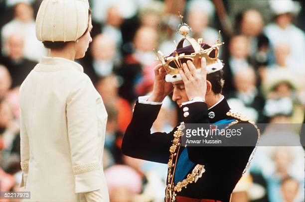 Prince Charles watched by HM Queen Elizabeth II places the gold coronet of The Prince of Wales on his head at his investiture as Prince of Wales on...