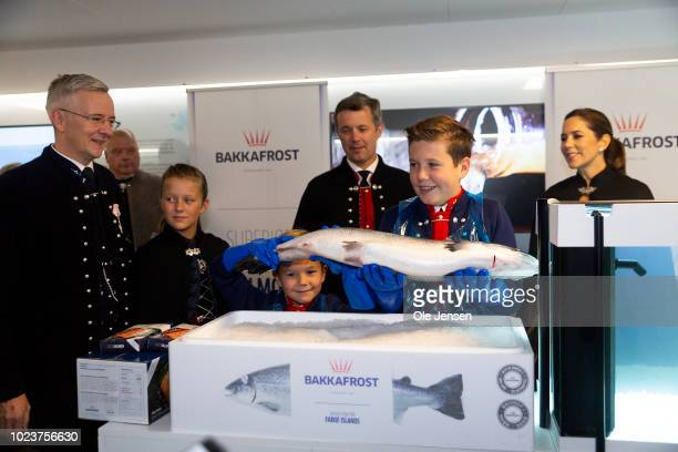 Prince Christian is presented a large salmon which he is asked to try and lift during the Crown Prince familys visit to the salmon producer...
