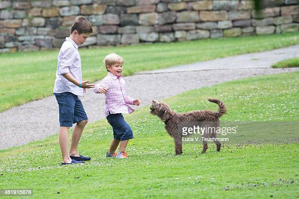 Prince Christian of Denmark and Prince Vincent of Denmark play with a dog during the annual summer Photocall for The Danish Royal Family at Grasten...