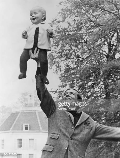 Prince Claus of the Netherlands holds up his eldest son WillemAlexander Prince of Orange at their home at Drakesteijn Netherlands September 1968