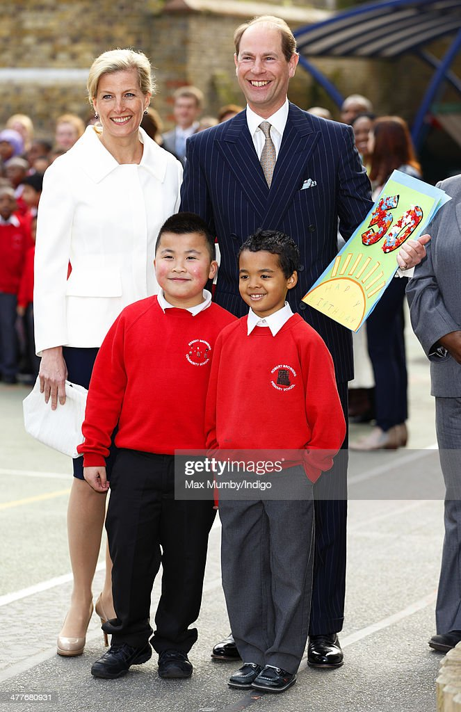 Prince Edward, Earl of Wessex accompanied by Sophie, Countess of Wessex receives a 50th birthday card from pupils during a visit to the Robert Browning Primary School, Walworth on March 10, 2014 in London, England.