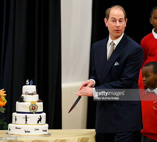 Prince Edward Earl of Wessex cuts into his 50th birthday cake which was presented to him during a visit to the Robert Browning Primary School...