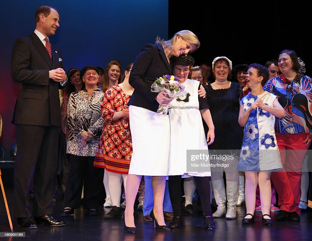 Prince Edward, Earl of Wessex looks on as Sophie, Countess of Wessex hugs a member of the cast after watching a performance during a visit to Shanklin Theatre on a day of engagements on the Isle of Wight on March 27, 2014 in Shanklin, England.