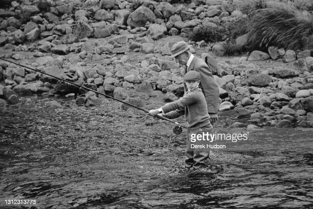 Prince Edward pictured wearing waders and a tweed cap being taught fly fishing with a ghillie in the River Dee in 1975