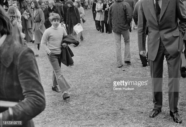 Prince Edward walks alone through a crowd at Windsor Home Park, 1975