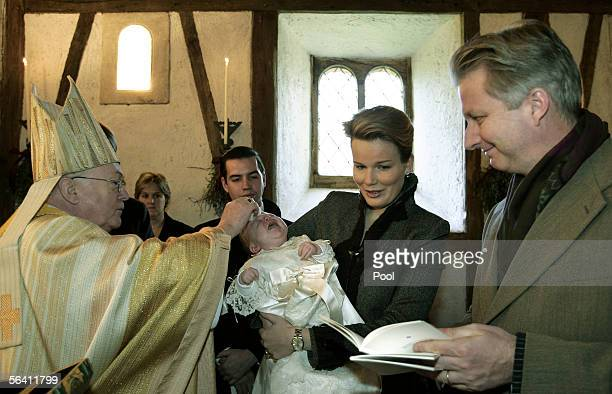 Prince Emmanuel is held by his mother Princess Mathilde as Belgian Cardinal Godfried Danneels performs a baptism ceremony while Crown Prince Philippe...