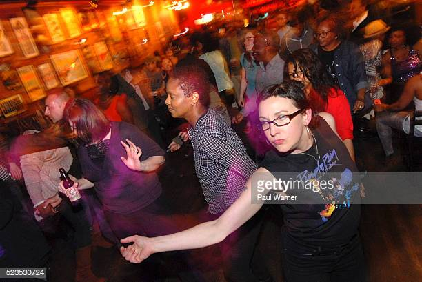 Prince fan Nancy Naperala sports a Purple Rain tee shirt as she dances at a celebration of his life at the Majestic Cafe on April 21 2016 in Detroit...