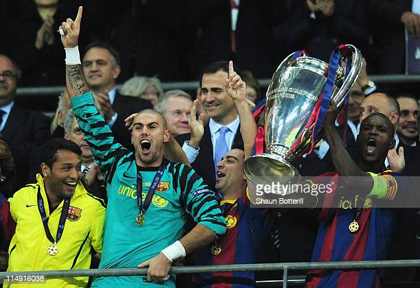 Prince Felipe Of Spain applauds as Eric Abidal of FC Barcelona lifts the trophy and celebrates with teammates after victory in the UEFA Champions...